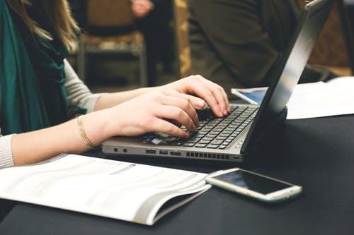 woman tying on laptop