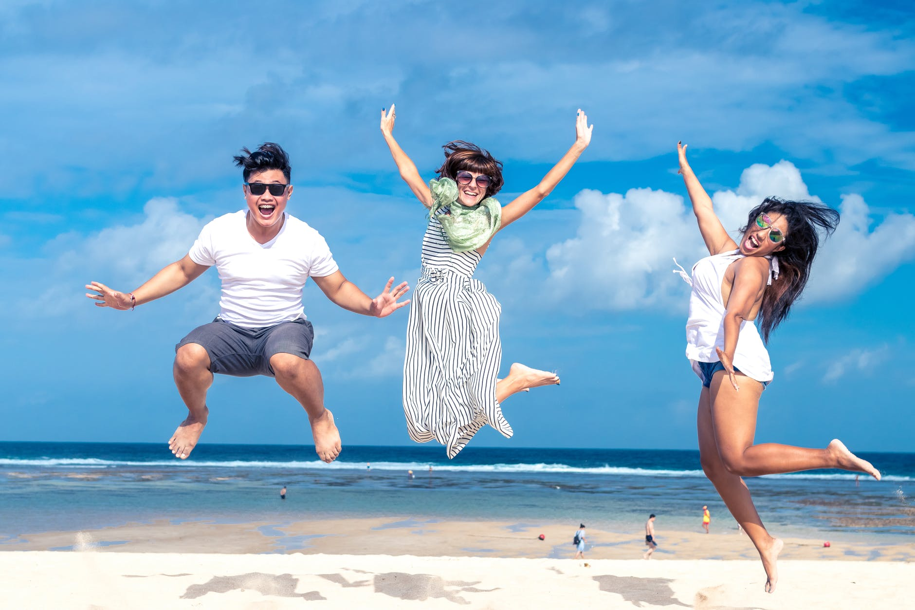 three friends jumping by the shore on the beach