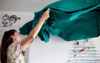 woman folding a green blanket