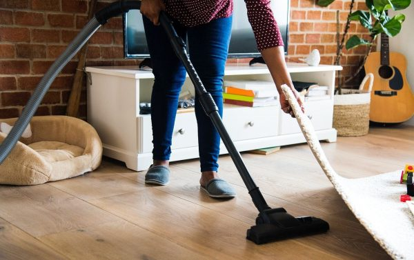 woman in jeans vacuuming underneath the carpet