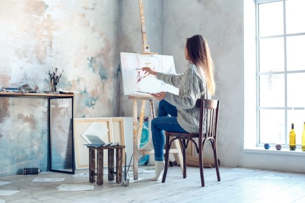 a woman in winter clothes painting a blank canvas