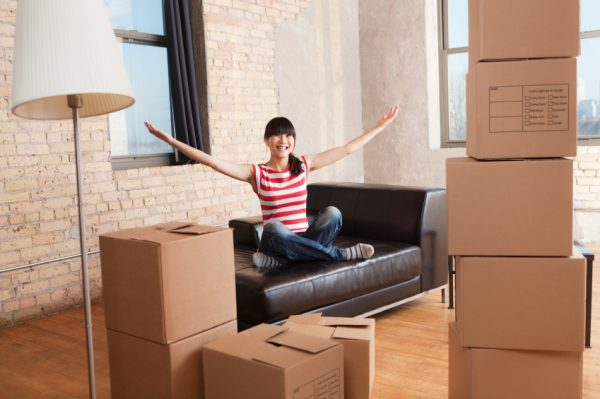 a woman sitting crossed legs on a couch while unpacking