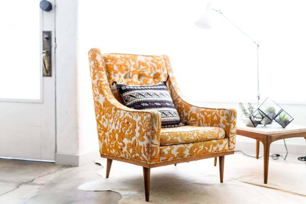 an elegant chair with yellow embroidered covers