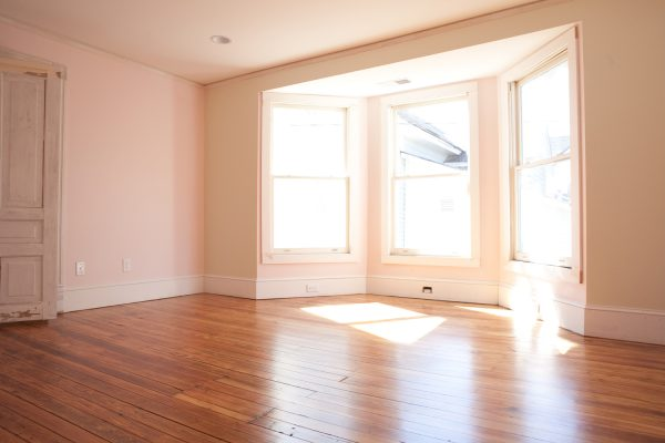 an empty room with wooden floors and a big window