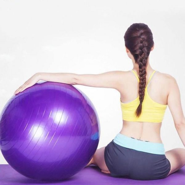 a woman sitting on a purple yoga mat holding a purple balance ball