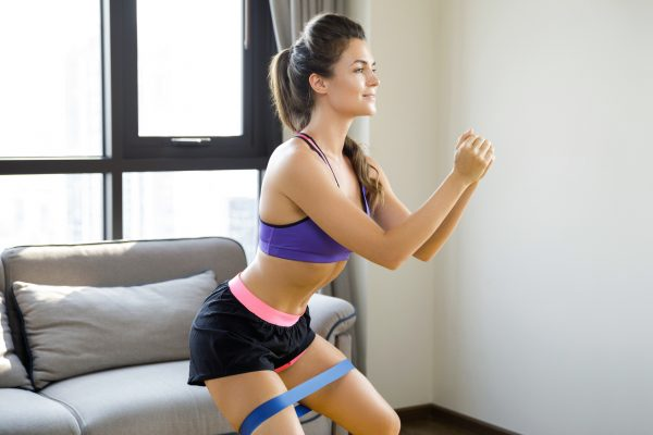 Beautiful woman during her home workout with a rubber resistance band