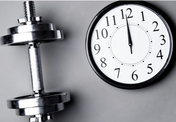 a stainless dumbbell beside a clock striking 12