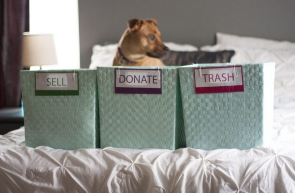 baskets laid out on the bed for sorting clothes to donate and throw away