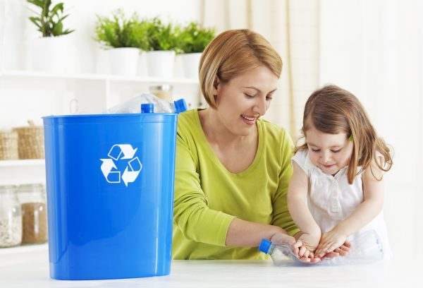 a mother teaching her daughter how to recycle a plastic bottle