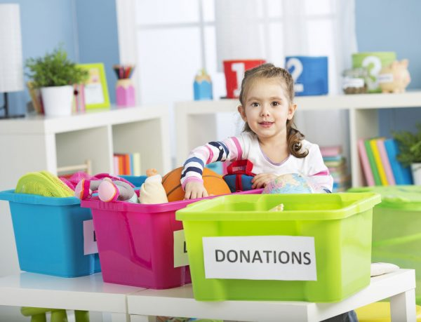 a girl sorting her toys out for donation