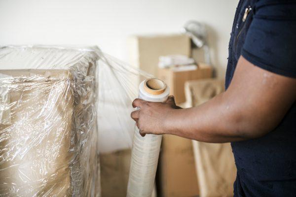 a black man wrapping a cardboard box with sirin wrap
