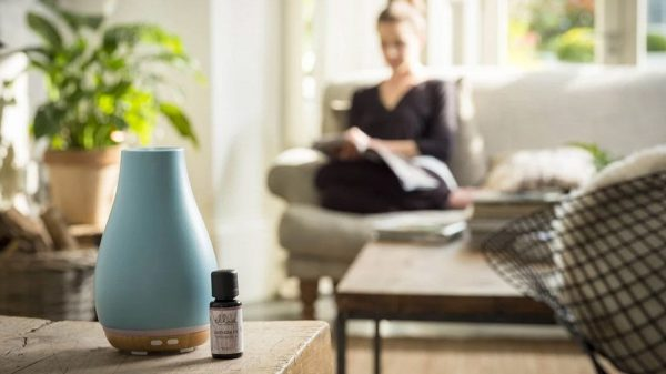 a woman reading a magazine in her living room while enjoying the aroma of essential oil