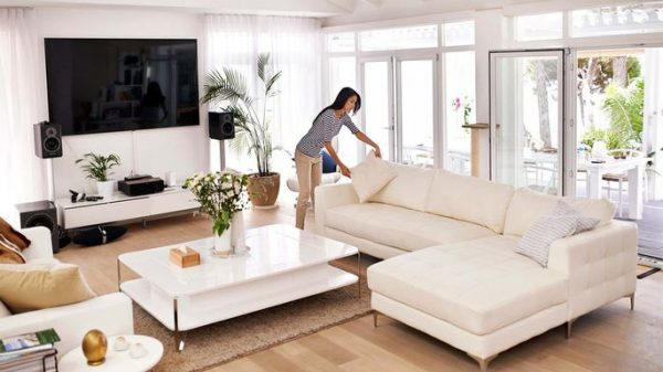 a woman arranging her living room and placing a throw pillow on a couch