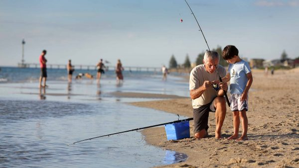 a father teaching his son to fish at the beach