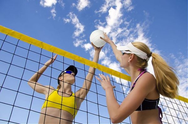 two women competing against each other in volleyball