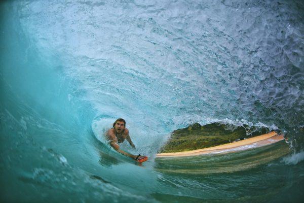 a man bodysurfing and enjoying the waves