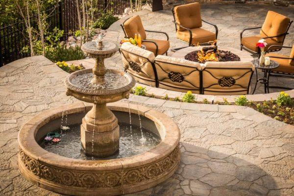 a backyard entertainment area with a fountain