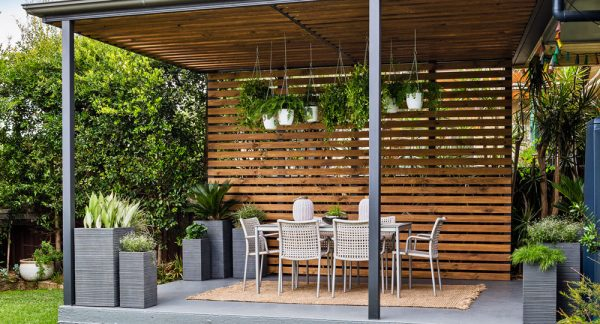a backyard entertainment area that features a tall pergola