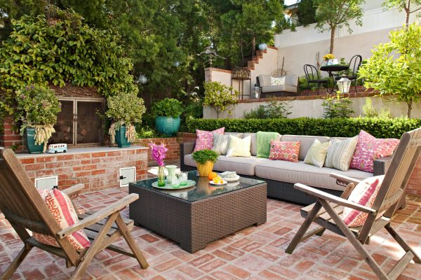 a backyard entertainment area with colorful throw pillows
