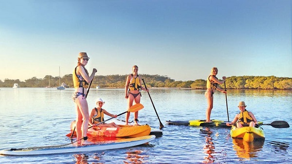 A group of friends paddle boarding