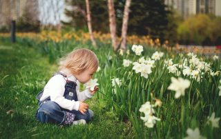 a toddler smelling the flowers