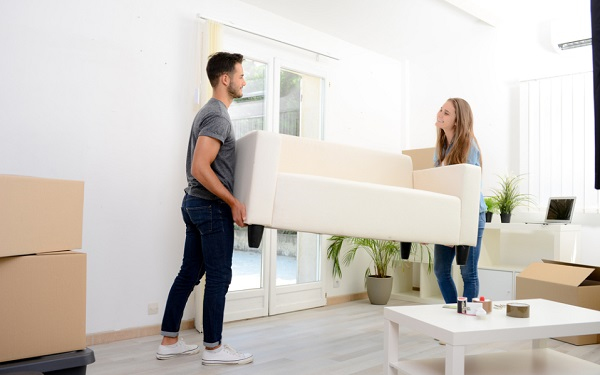 A couple moving a sofa